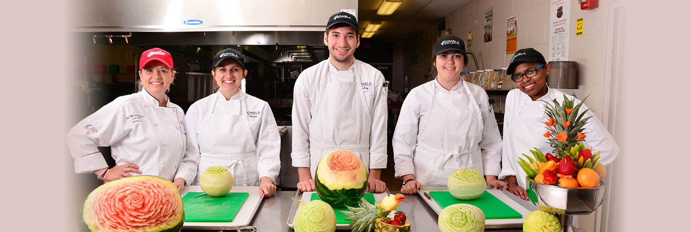 Culinary students with decoratively-carved melons and fruit displays