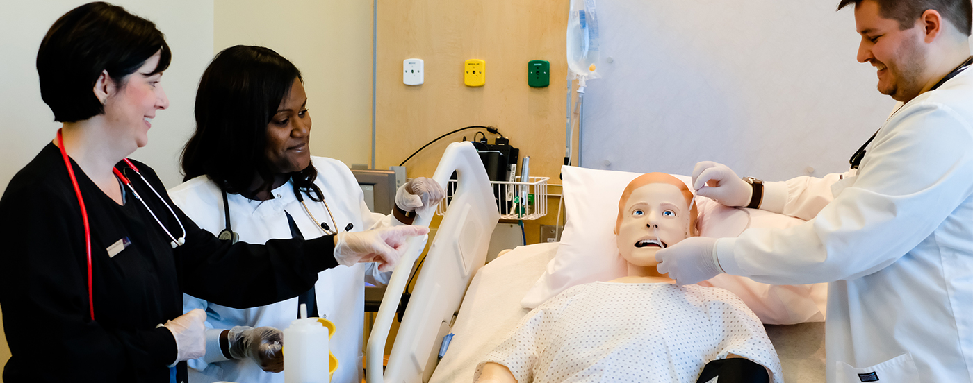 Nursing program students and instructor with mannequin patient