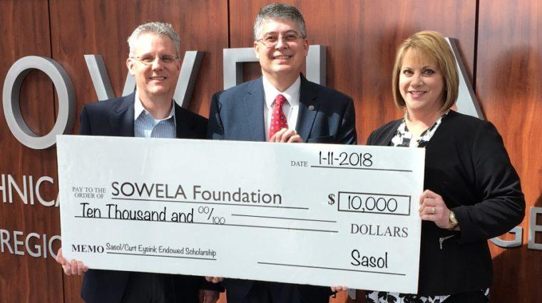 Michael Kane, Dr. Neil Aspinwall, and Gina Jones holding a $10000.00 check